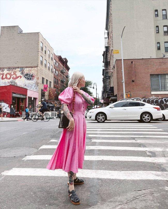 Jovem de lado posando em faixa para pedestre, ela usa um vestido longo cor de rosa e uma bolsa preta.