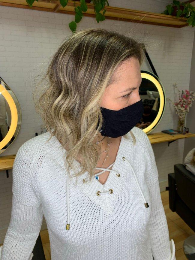 Mulher com o rosto virado para o lado direito e usando blusa branca. Atrás dela, podemos ver espelhos pendurados na parede.