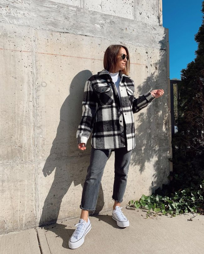 Jovem posando com casaco xadrez e tênis plataforma. Ela usa óculos escuros e olha para o lado direito.