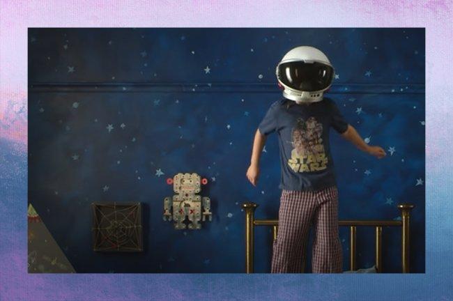Quarto de Auggie, do filme Extraordinário; ele aparece pulando na cama com camiseta do Star Wars, calça quadriculada em branco e vermelho e capacete de astronauta na frente da parede azul escura com desenhos de estrelas; no canto da imagem é possível ver uma cabana e um item de decoração no formato de um rôbo na cor cinza com detalhes vermelhos pendurado na parede assim como um quadro com linhas brancas e detalhes vermelhos; a margem é uma textura degradê de rosa, branco, azul, lilás e roxo