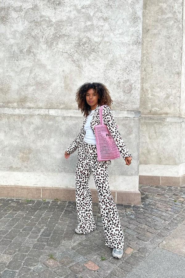 Foto de uma mulher em uma calçada. Ela usa o cabelo solto, camiseta branca, casaco branco com estampa de bolinhas pretas, calça com a mesma estampa, tênis e bolsa rosa de crochê da Prada. Ela olha para a câmera e não sorri.