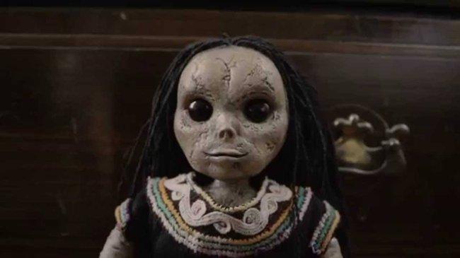 Foto da Boneca do Mal. Ela tem muitas cicatrizes no rosto, é cinza e usa um vestido antigo