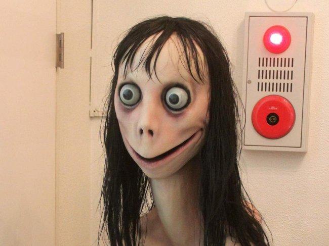 Foto da boneca Momo. Ela tem um sorrido maligno de orelha a orelha, olhos esbugalhados e cabelo preto