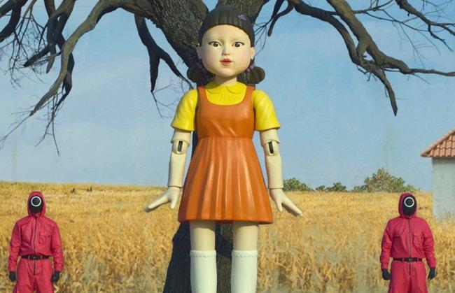 Boneca da série Round 6. Ela tem franja e usa um vestido laranja