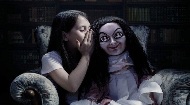Foto de divulgação do filme A Boneca Maldita. Uma criança sussurra no ouvido do brinquedo, que tem longos cabelos pretos e um olhar penetrante