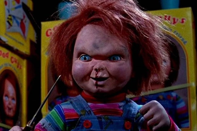 Foto do Chucky, o brinquedo assassino. Ele é ruivo, usa um macacão jeans, segura uma adaga e tem sangue escorrendo do nariz