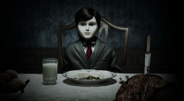 Foto do Boneco do Mal. Ele é pálido, veste um terno e está sentado na mesa de jantar