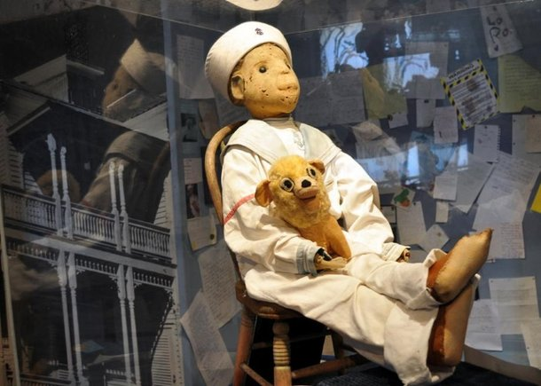 Foto do boneco Robert. Ele tem roupas de marinheiro e está sentado em uma cadeirinha de madeira