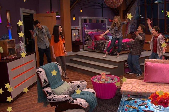 Quarto da Carly, de iCarly; ela está olhando chocada para o cômodo enquanto os outros personagens estão erguendo os braços com empolgação ao revelar o ambiente para ela; Spencer está ao lado de Carly, que usa uma blusa laranja, segurando a maçaneta da porta; o ambiente é decorado com detalhes em rosa, azul roxo e cinza sendo que uma escada de três degraus leva para a cama; estrelas amarelas decoram a imagem