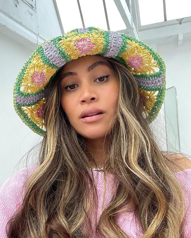 Selfie de uma mulher. Ela usa uma blusa rosa, cabelo solto, maquiagem básica e chapéu de crochê colorido. Ela olha para a câmera e não sorri.