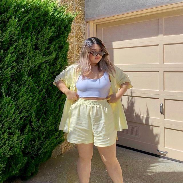 Foto de uma mulher em uma garagem. Ela usa um top cropped branco, camisa de manga curta amarela e short amarelo. Ela está com as duas mãos na cintura, olha para o lado e sorri levemente.