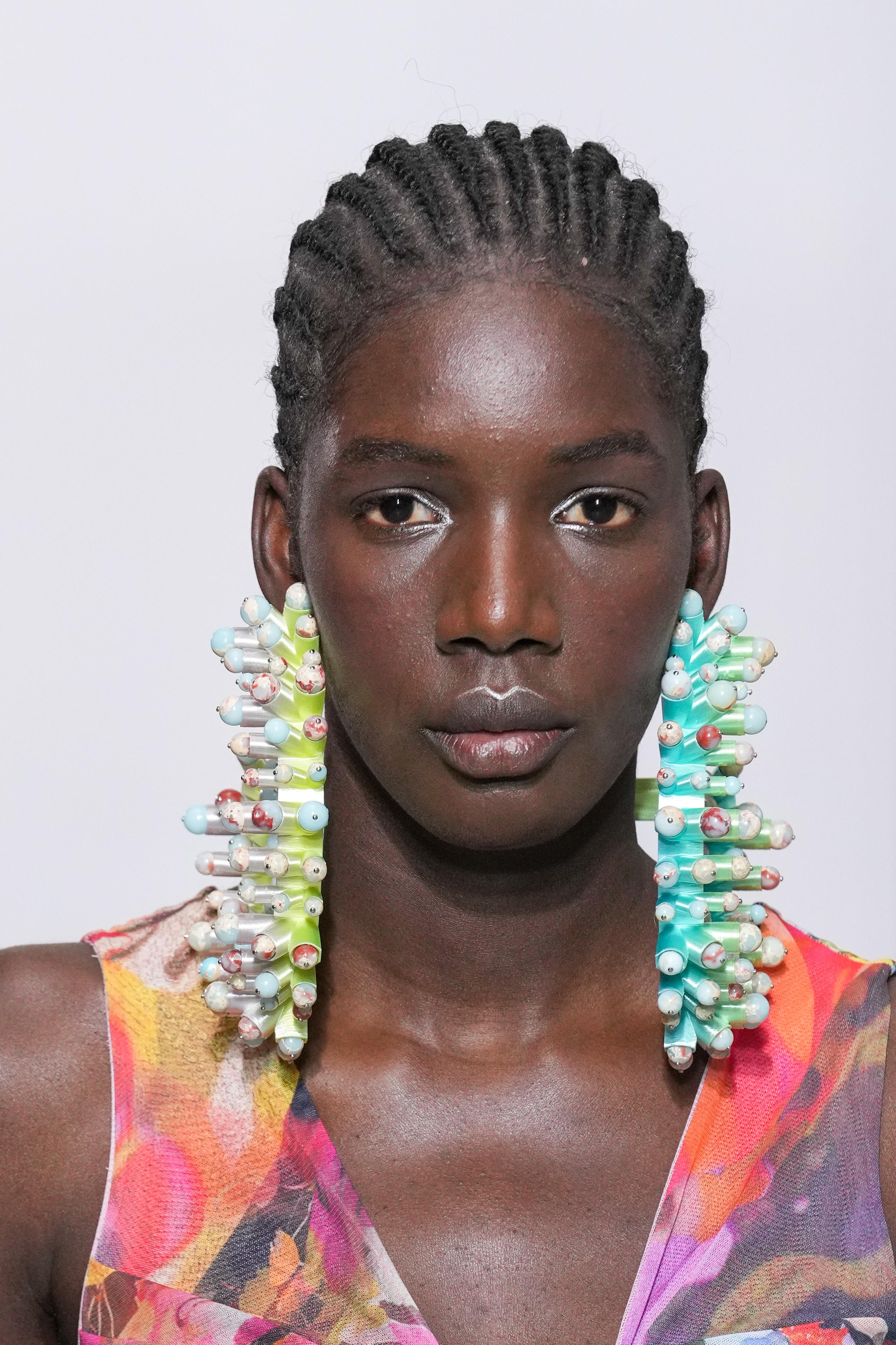 Rosto de modelo com brincos compridos e diferentões no desfile de primavera-verão da Maitrepierre na semana de moda de Paris