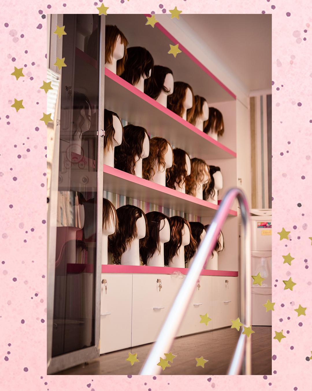 Foto de várias perucas em prateleiras que ficam dentro do Banco de Perucas Móvel, da ONG Cabelegria, em fundo rosa com bolinhas e estrelas douradas