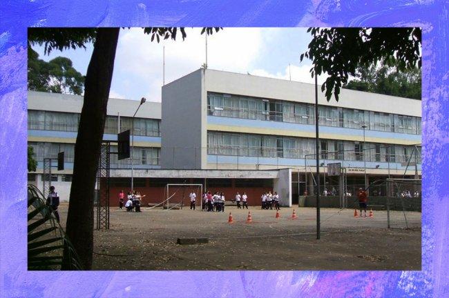 Foto da fachada de uma escola estadual de São Paulo. O prédio tem dois andares e alguns estudantes brincam na quarta descoberta em frente a ele