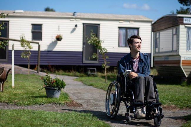 Foto do Isaac, personagem de Sex Education, em frente ao seu trailer. Ele olha para o lado e está sentado em sua cadeira de rodas