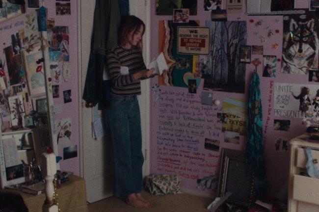 Quarto de Lady Bird, do filme Lady Bird, produzido pela A24; ela está encostada na porta branca do quarto, que tem roupas penduradas, abrindo um envelope de carta branco com expressão séria; as paredes do cômodo são rosa com pôsteres, frases e desenhos preenchendo o ambiente; um espelho de corpo inteiro está ao lado da porta; a personagem usa calça jeans, blusa listrada e está descalça olhando para os papéis em sua mão