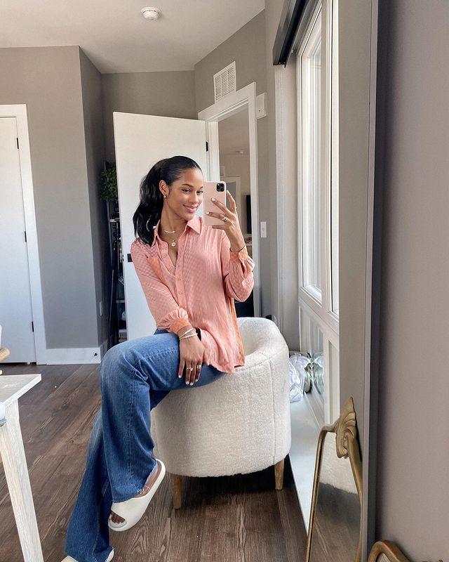 Selfie de uma mulher em um espelho sentada no braço de uma poltrona. Ela usa uma camisa rosa de manga longa, calça jeans e chinelo slide. Ela olha para o celular e sorri.