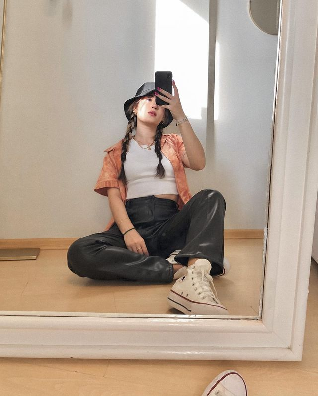 Selfie no espelho de uma mulher sentada no chão. Ela usa uma camiseta branca, camisa laranja tie dye como sobreposição, calça de couro preta, tênis branco de cano alto e bucket hat. Ela olha para o celular e não sorri.