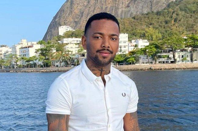 Imagem de Nego do Borel sorrindo levemente; ele está usando uma camisa branca e o fundo da imagem mostra o mar e parte do morro do Pão de Açúcar no Rio de Janeiro