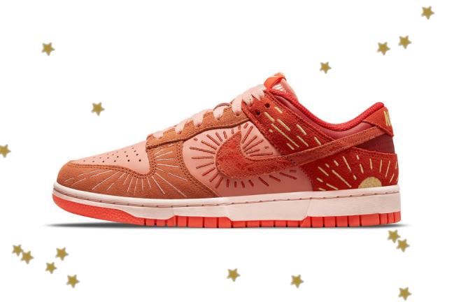 Foto com fundo branco e com estrelinhas douradas. No centro, temos o novo tênis da Nike do modelo Dunk Low com as cores laranja, vermelho e detalhes em amarelo.