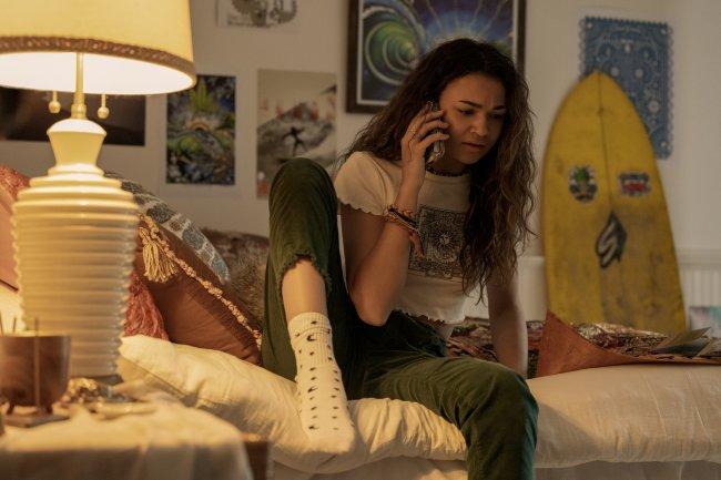 Madison Bailey como Kiara em cena de Outer Banks; ela está sentada na cama conversando no celular usando uma calça verde com blusa branca e meia branca com detalhes; a parede branca está repleta de quadros e uma prancha amarela está encostada no fundo; um abajur ilumina o cômodo com luz amarela