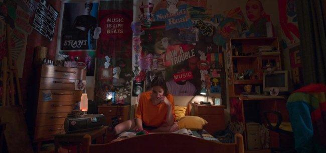 Eda, da série Love 101, estudando sentada na cama com uma camiseta laranja; a iluminação do cômodo vem de um abajur e as paredes estão cobertas por pôsteres e desenhos