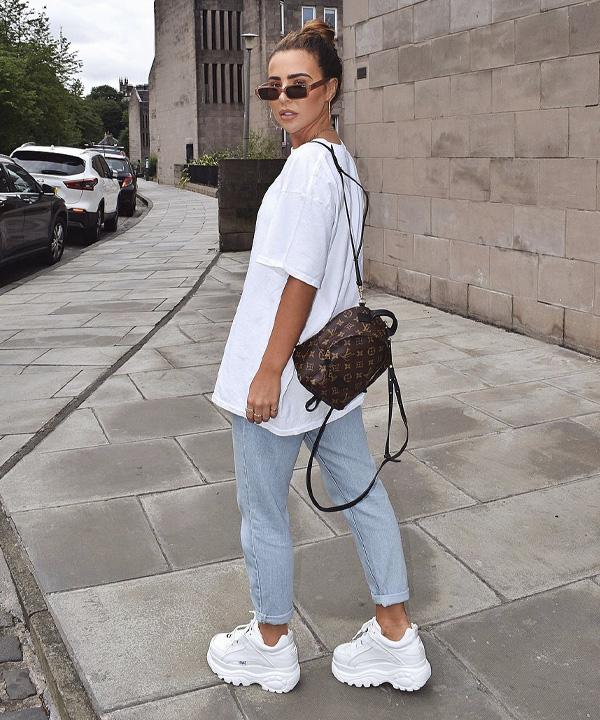 Jovem posando virada de costas com a bolsa pendurada, ela usa calça jeans e tênis branco.