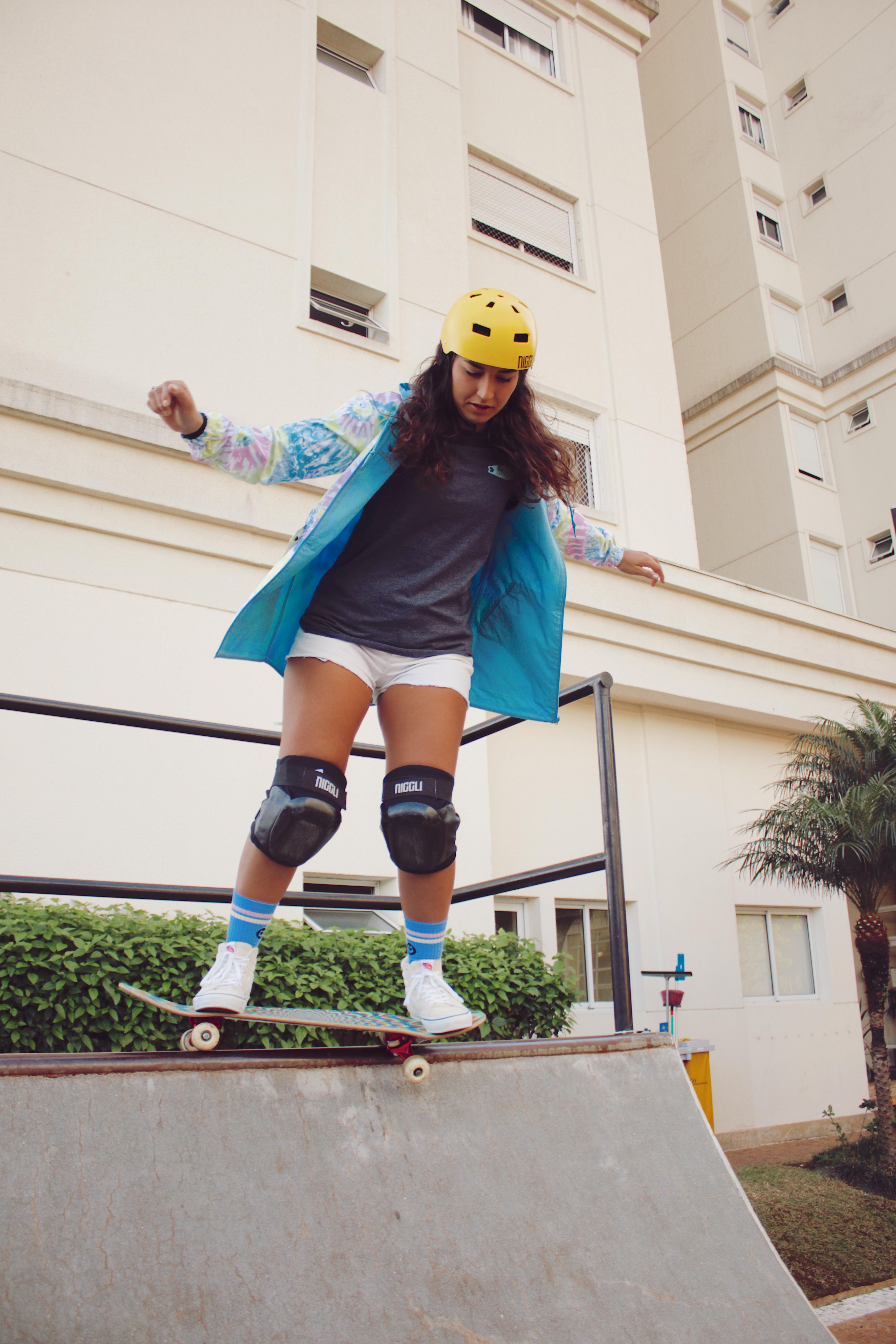 Thais Gazarra andando de skate em uma mini rampa com jaqueta azul, camiseta cinza, short e capacete e joelheira