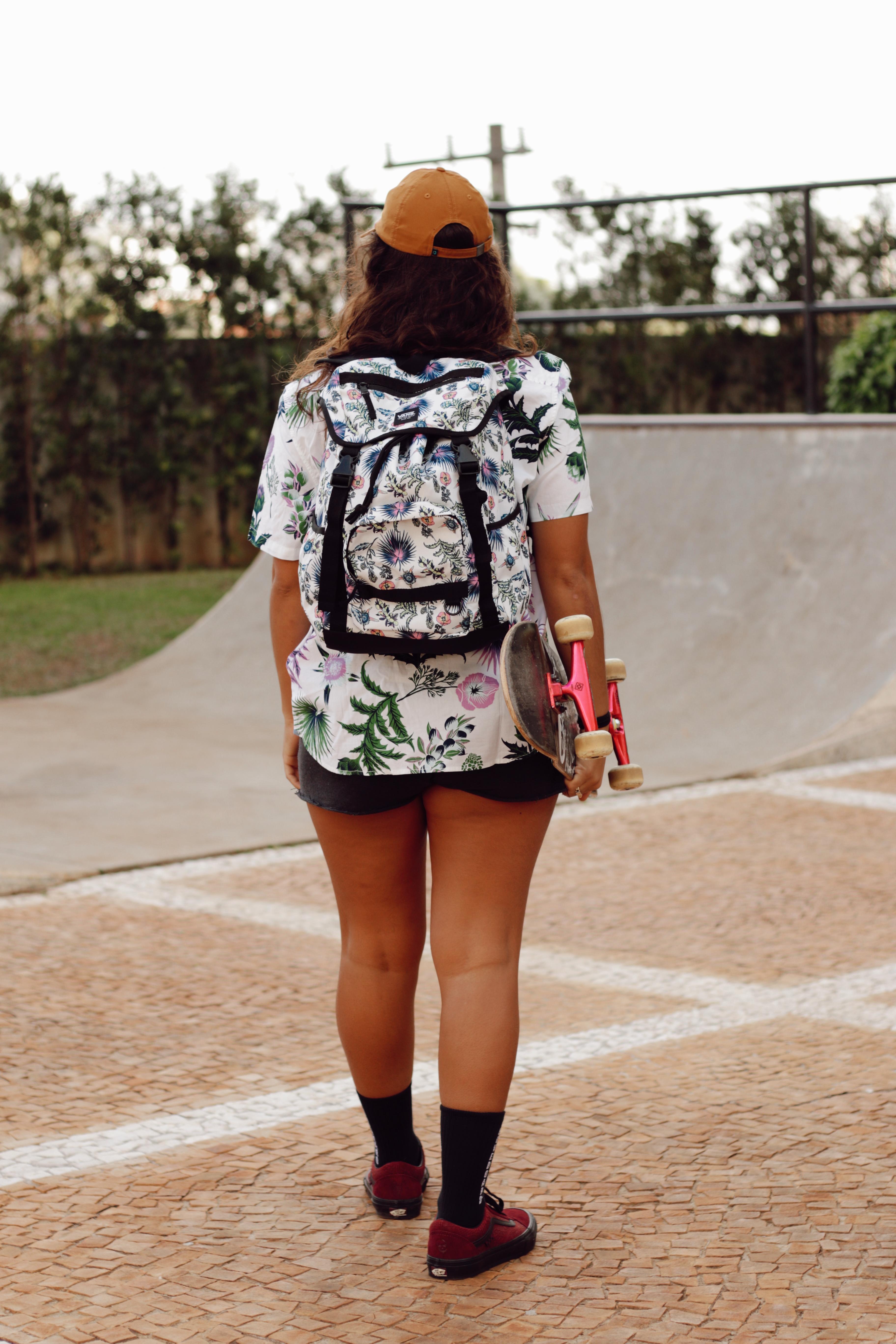 Thais Gazarra de costas, carregando o skate com uma das mãos, usando camisa floral de manga curta, mochila, tênis e meia de cano alto