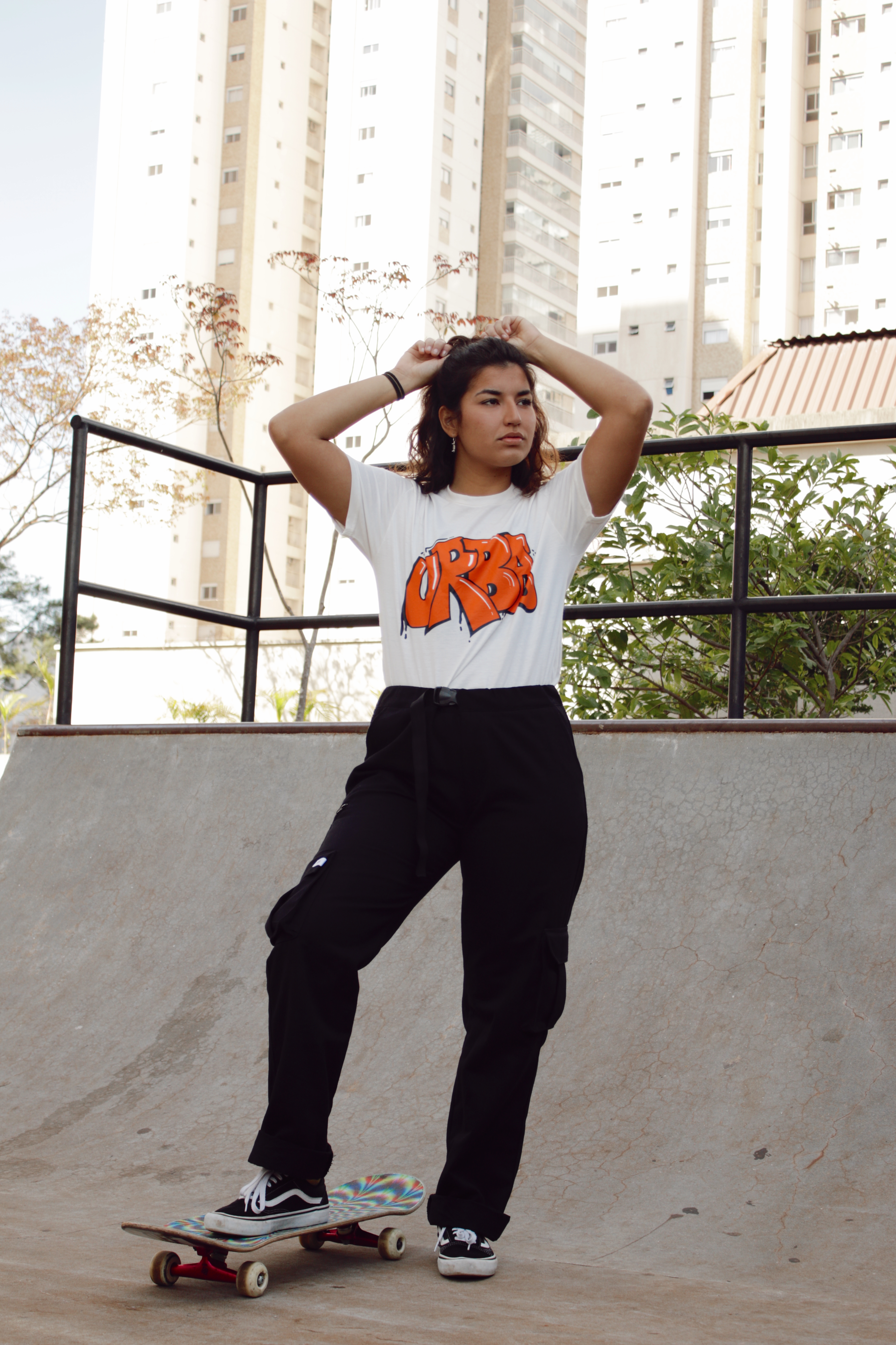 Thais Gazarra em mini rampa de skate usando camiseta branca, calça cargo preta, com um dos pés apoiado no skate e mexendo no cabelo com as duas mãos para trás