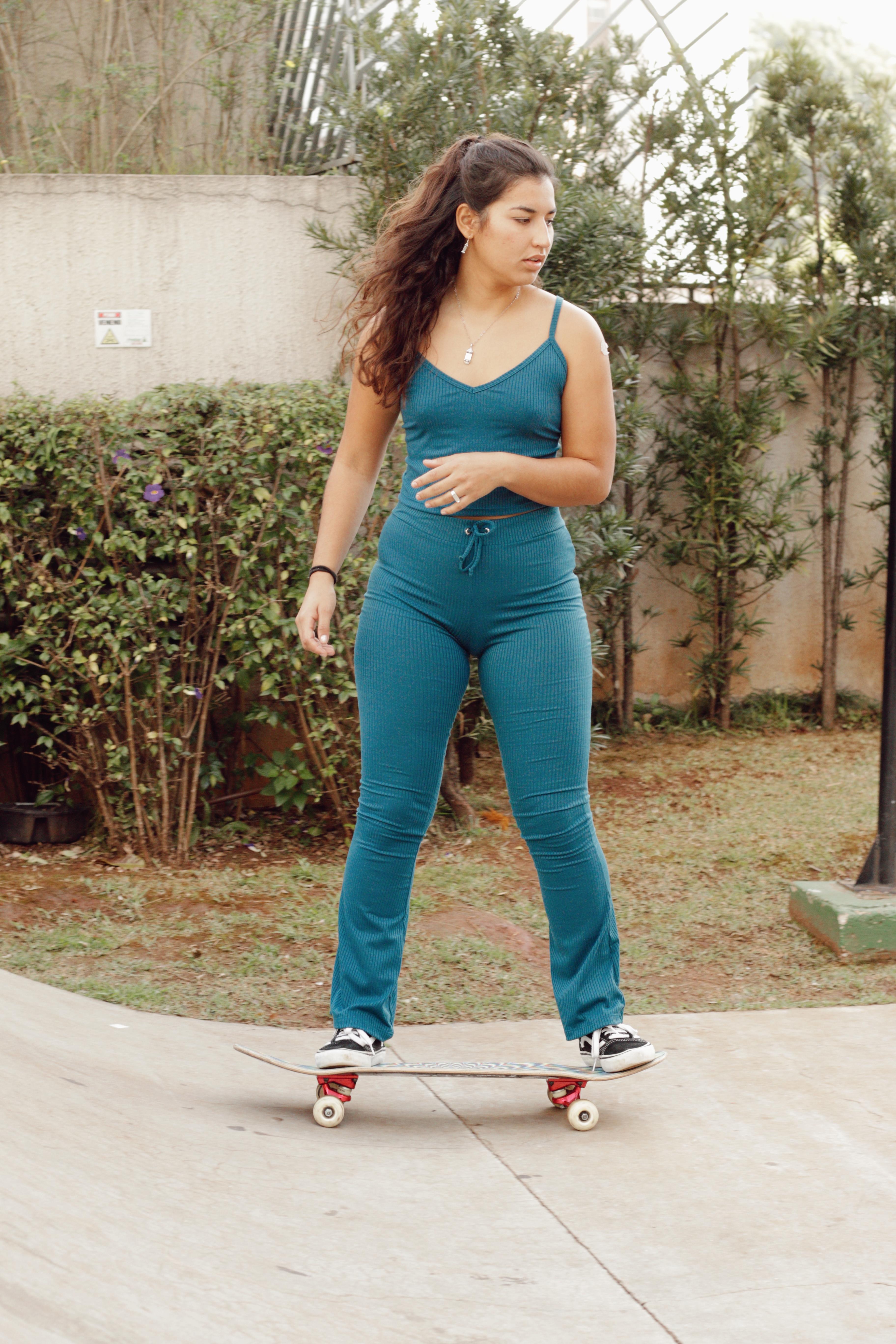 Thais Gazarra usando conjuntinho de regata e calça azuis enquanto anda de skate