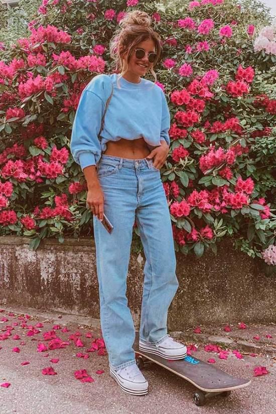 Jovem posando em frente a parede com flores cor de rosa. Ela posiciona a mão direita no bolso e usa calça jeans.