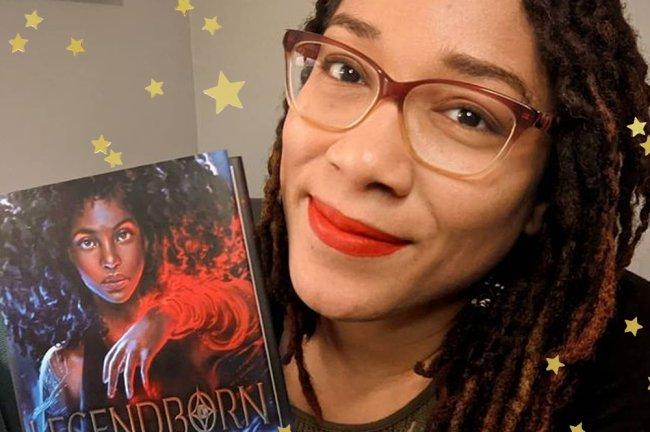 Selfie de Tracy Deonn, autora do livro Lendários, segurando a versão da obra em inglês; ela sorri levemente e está usando óculos e batom vermelho; estrelas amarelas decoram a imagem