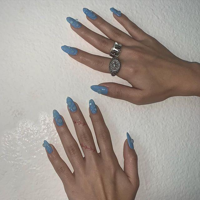 Foto de duas mãos com as unhas longas pintadas de azul e detalhe 3D imitando gotas de água.