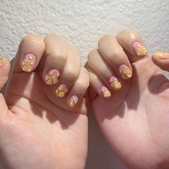 Foto de duas mãos com o esmalte degradê de rosa e amarelo com detalhe de gota de água em gel 3D.