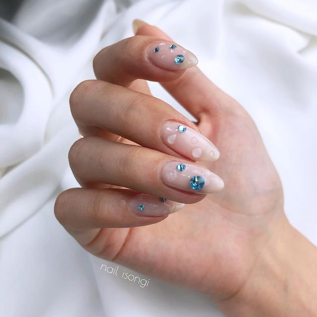 Foto de uma mão com as unhas longas e detalhe de brilho azul e gotinhas de água de gel 3D.