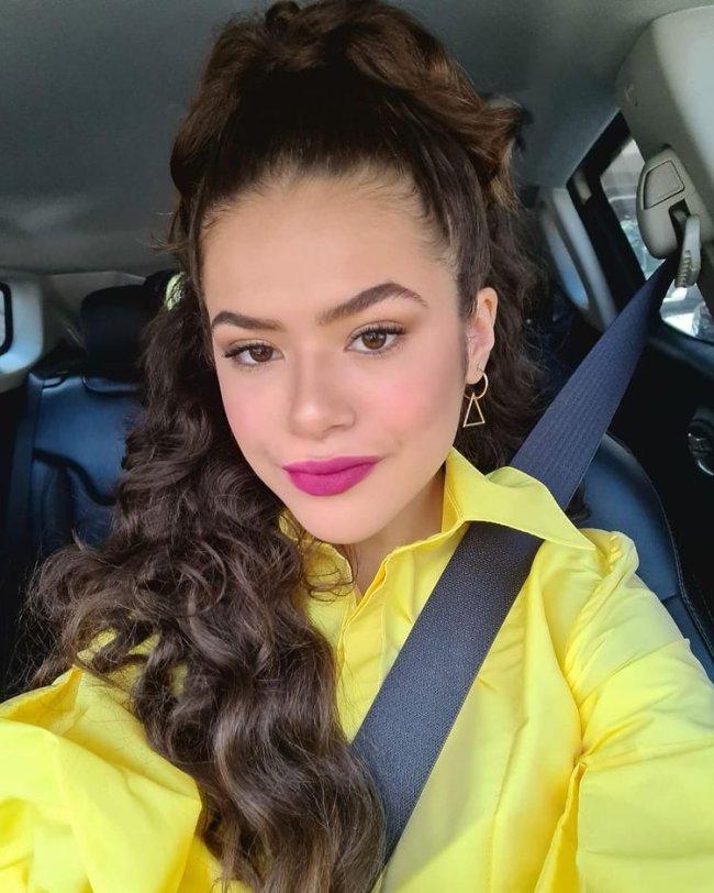 Maisa posando para selfie dentro do carro, podemos ver o cinto de segurança, e ela usando blusa amarela com penteado meio preso e expressão sorridente.