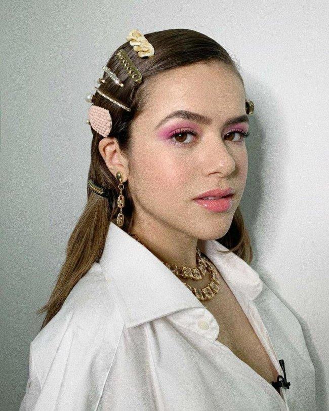 Maisa usando mix de presilhas com fundo branco e expressão séria, ela usa camiseta da mesma cor.