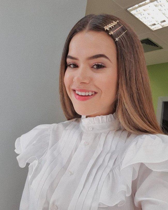 Maisa posando sorridente com blusa de gola alta branca e mix de presilhas na lateral do seu cabelo.